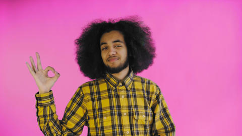 Smiling attractive Afro-American guy showing ok gesture while standing isolated Footage