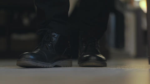 Close-up men's legs in black shoes enter a restaurant or cafe through opening Archivo