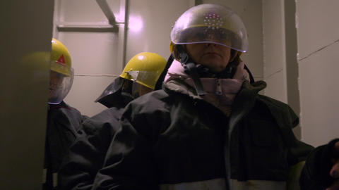Women rescuers in protective suits and helmets going in tunnel with hand Footage