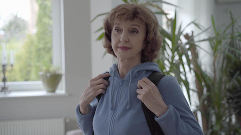 Portrait mature woman in blue hoody fixing black comfortable backpack at her Footage
