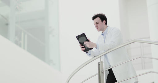 Male Doctor in Hospital looking at test results on a digital tablet Footage
