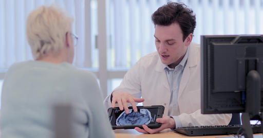 Male Medical Doctor explaining scan results to patient Footage