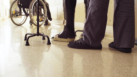 Legs of invalid in orthosis walking with support of two walking cane Footage