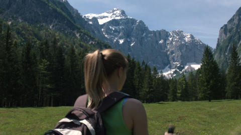 Back view of young woman hiking alone in the mountains, closeup Footage