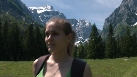 Front view of young woman hiking alone in the mountains, closeup Footage