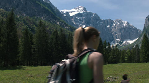 Back view of young woman hiking alone with snowy mountain in the background Footage