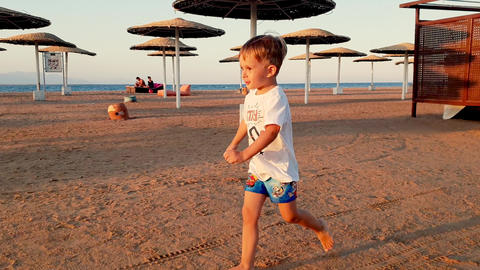 4k footage of happy cheerful boy running on the beach at sunset Footage