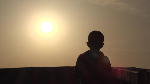 Silhouette boy, children is prying and sun. Dream, hope, religion and boyhood concept Footage
