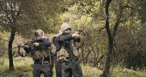 Squad of armed islamic isis terrorists patrolling a forest area during combat Live Action
