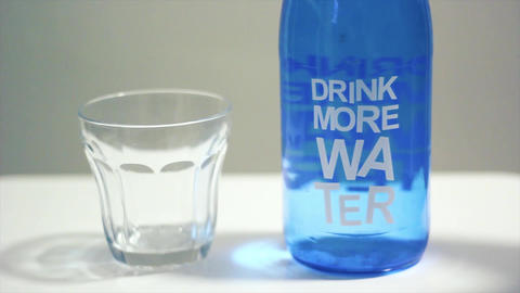 "A glass of water. Woman filling water to glass from bottle which has a text ""Drink more water"" Live Action"