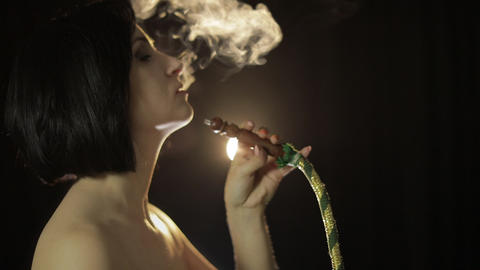 Beautiful, naked woman smoking hookah. Attractive girl smoking flavored tobacco Live Action