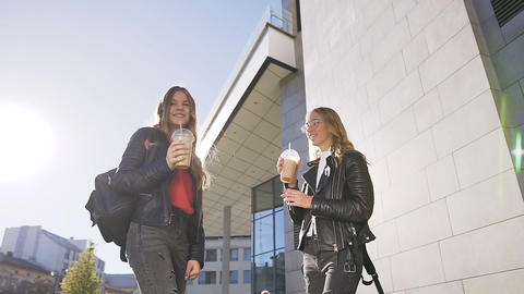 Two young girls drinking of cold fresh juice while walking outdoors on sunny Footage