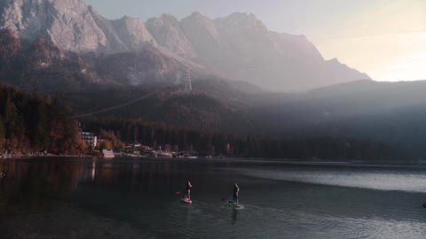 Two paddle boarding people on beautiful lake with huge alp mountains in the background 4K Footage