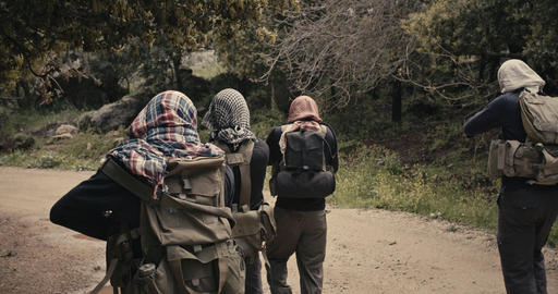 Squad of armed islamic isis terrorists patrolling a forest area during combat Footage