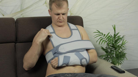 Painful, bored man with a broken arm wearing arm brace… Stock Video Footage