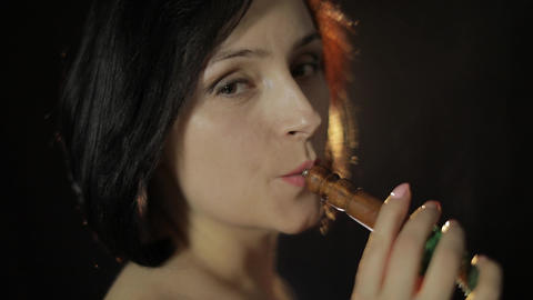 Beautiful, young woman smoking hookah. Attractive girl smoking flavored tobacco Live Action