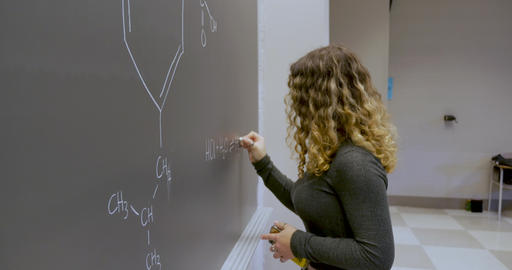 Young female student holding a smartphone writing on a chalkboard and writing the answers to a Live Action