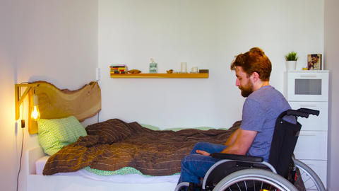 Disable man is changing wheelchair for a bed Live Action