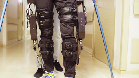 Legs of invalid in robotic exoskeleton walking through the corridor Footage