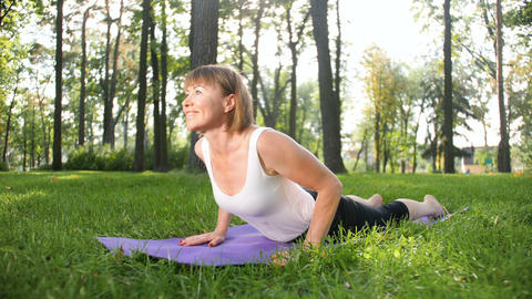 4k footage of middle aged woman exercising in park. Adult female practising yoga Footage
