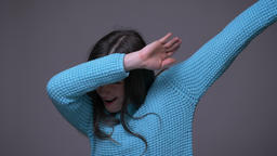 Closeup shoot of young cool brunette female dabbing with confidence looking at Footage