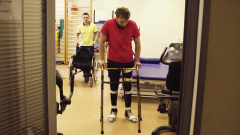 Disabled man in orthosis walking holding a walking frame Live Action