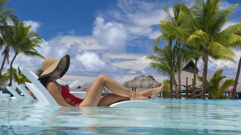 Luxury hotel swimming pool woman relaxing in lounging chair on summer vacation Footage
