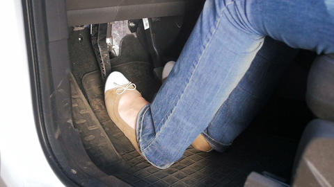 Closeup slow motion video of female drivers feet in comfortable shoes pressing ビデオ