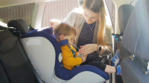 4k video of young mother seating her little son in child safety seat and adjusts Footage