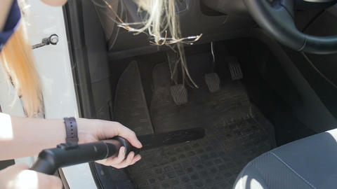 Slow motion video of young woman using hoover to clean her car interior from Footage