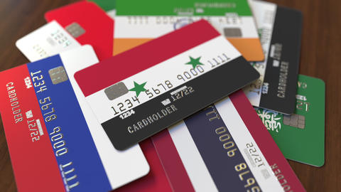 Many credit cards with different flags, emphasized bank card with flag of Syria Footage