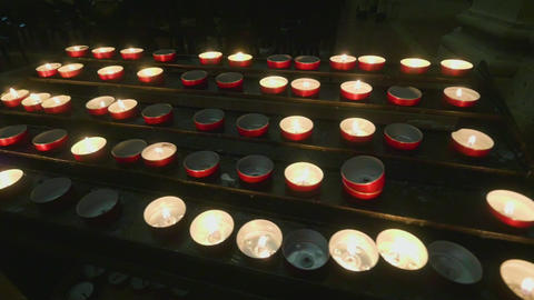 Support with lit candles inside a dark church Footage