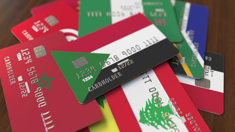 Many credit cards with different flags, emphasized bank card with flag of Sudan Footage