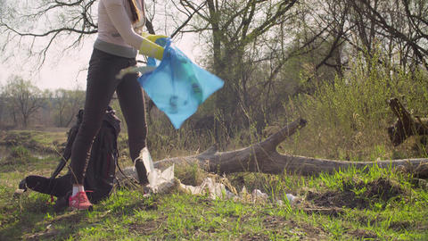 Woman green activist collecting garbage in the forest Footage