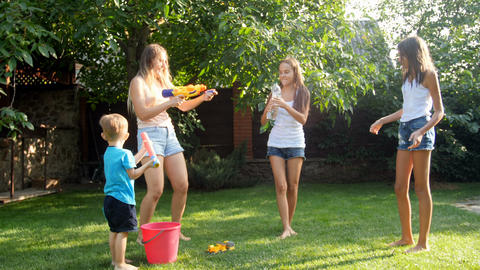 Slow motion video of family having water battle with garden hose and water guns Footage
