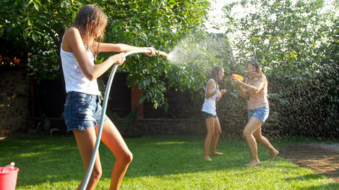 4k footage of happy cheerful teenagers playing in garden with water guns and Footage
