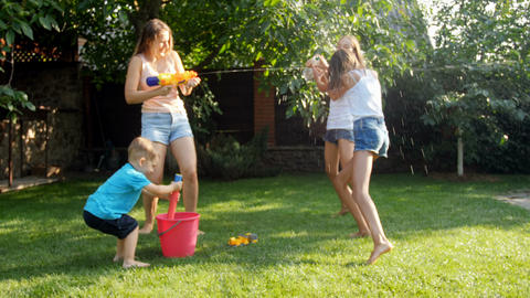 Slow motion video of happy children and adults splashing water from water guns Footage