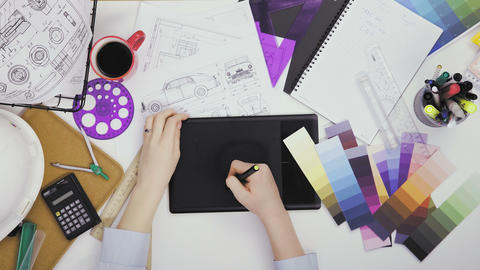 Creative designer using graphics tablet while working at her table Live Action