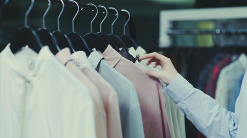 Close up of Woman is touching hangers with blouses in showroom Footage