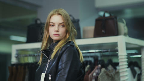 Young beautiful girl trying on a leather jacket in the store Footage