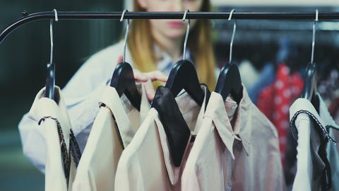 Woman is touching hangers with blouses in showroom Footage