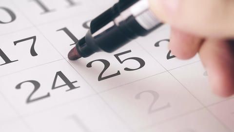 Marking the twenty-fifth 25 day of a month in the calendar with a red marker Footage