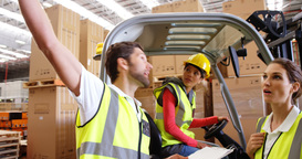 Warehouse workers interacting with forklift driver Footage
