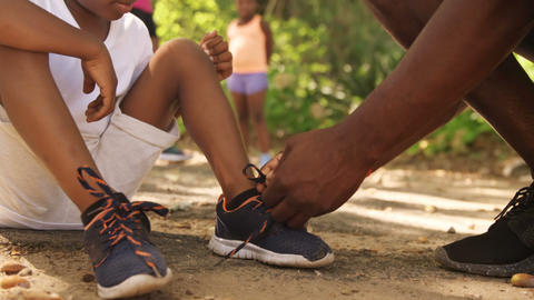 Close up of father is doing his son shoelaces Live Action