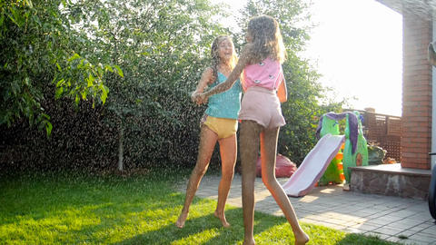 Slow motion video of two cheerful girls dancing and jumping under water from Live Action