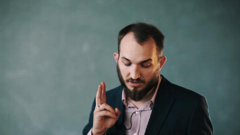 Bearded man in jacket and striped shirt gesturing making point on isolated wall Live Action