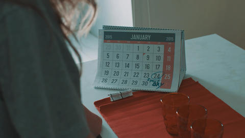Woman looking at calender of january 2015, 24 date circled with mark sport day Footage
