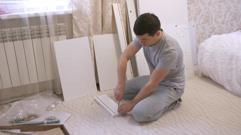 Man assembling wooden parts of furniture Footage