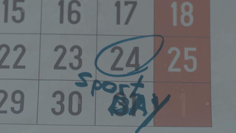 Part of calendar sheet with marked date as sport day with... Stock Video Footage