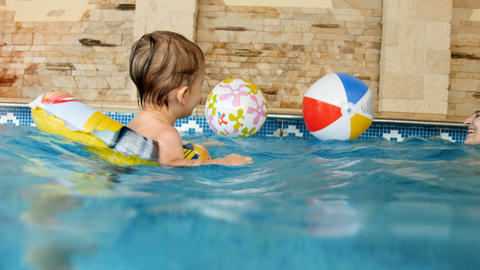 4k video of smiling toddler boy swimming in pool with inflatable ring and Live Action